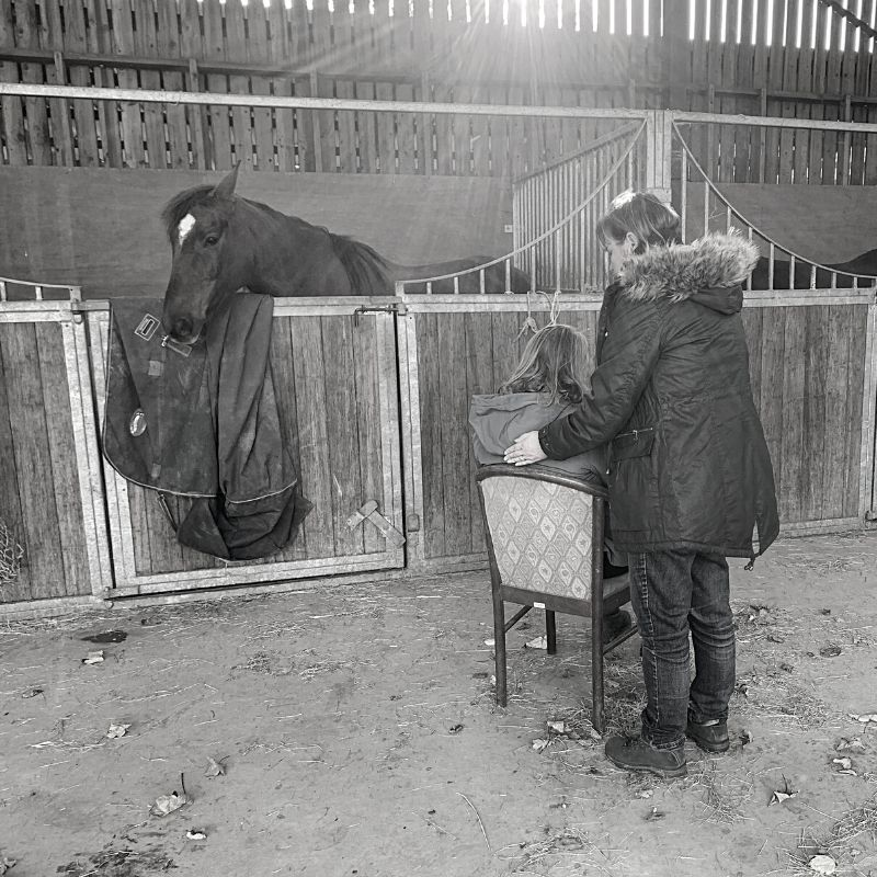 Black and white picture of a lady on a chair in a stable