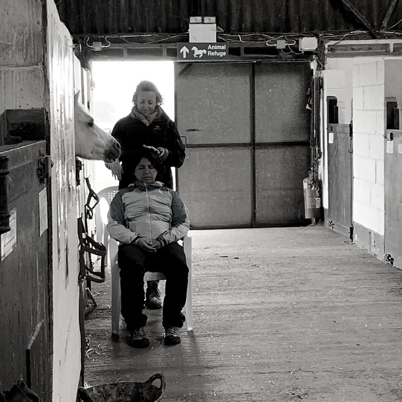 Black and white picture of Ali in a stable giving reiki to a lady sat on a chair