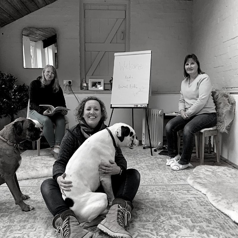 Black and white picture of Ali with a dog sat in her lap