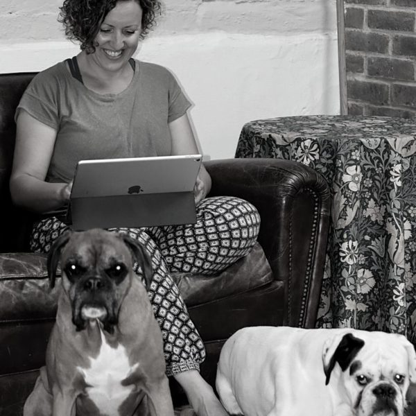 Black and white picture of Ali sat with a computer and dogs sat in front of her