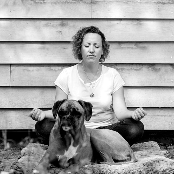 Black and white picture of Ali meditation with a dog sat in front of her