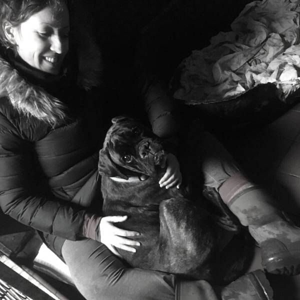 Black and white picture of Ali with a black dog in her lap who is looking up at the camera